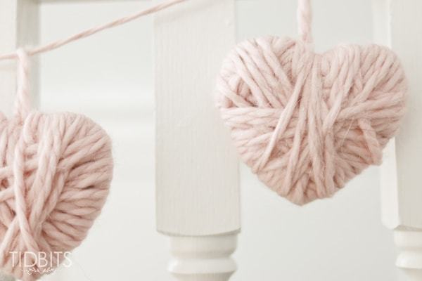 two light pink yarn hearts on a banner against white stair posts