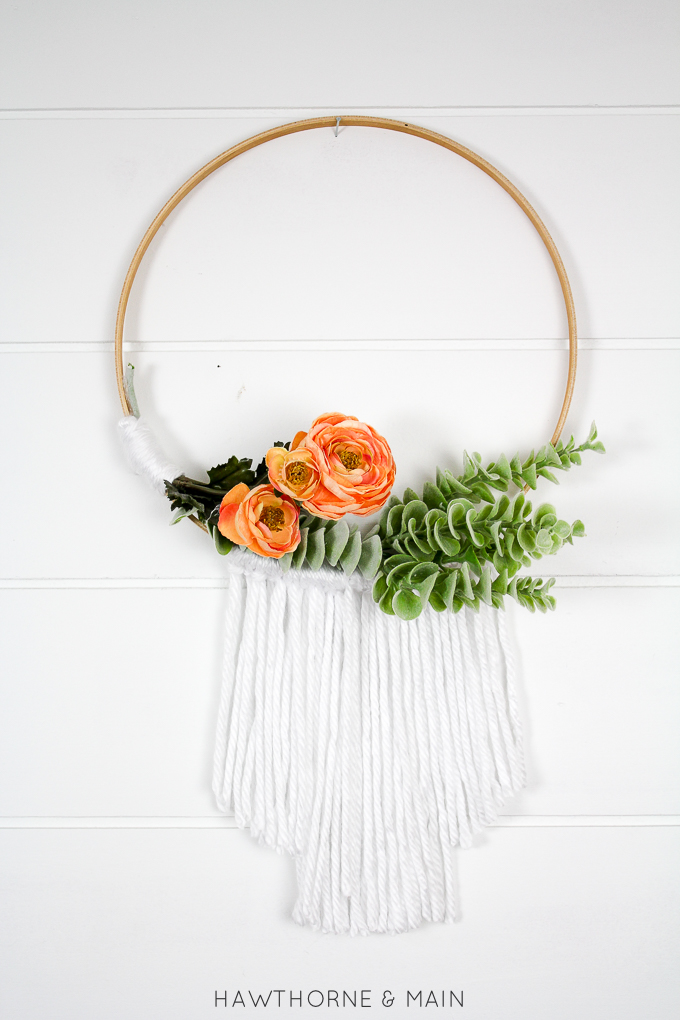 embroidery hoop wall hanging with white yarn on the bottom. orange flowers and greenery