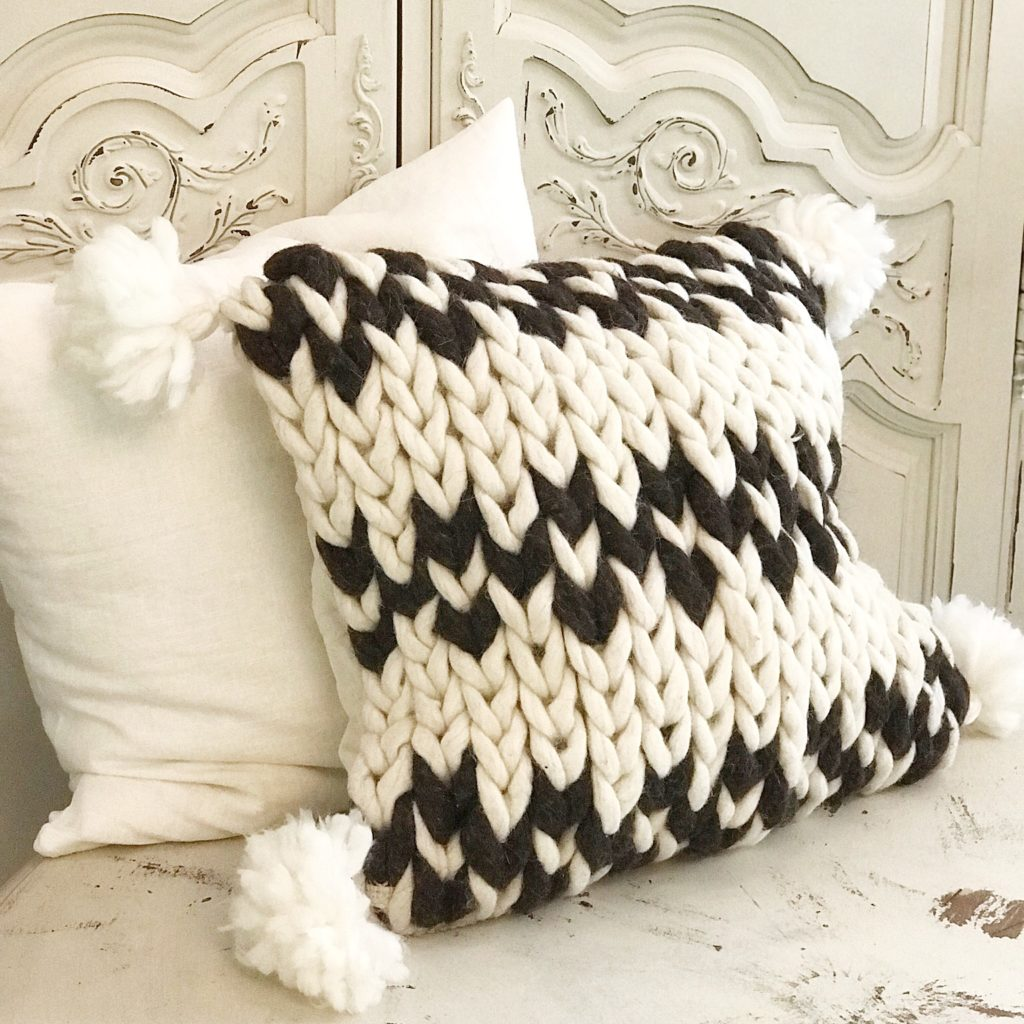 white and black chunky wool knit pillow with white tassels on corner leaning against white linen pillow