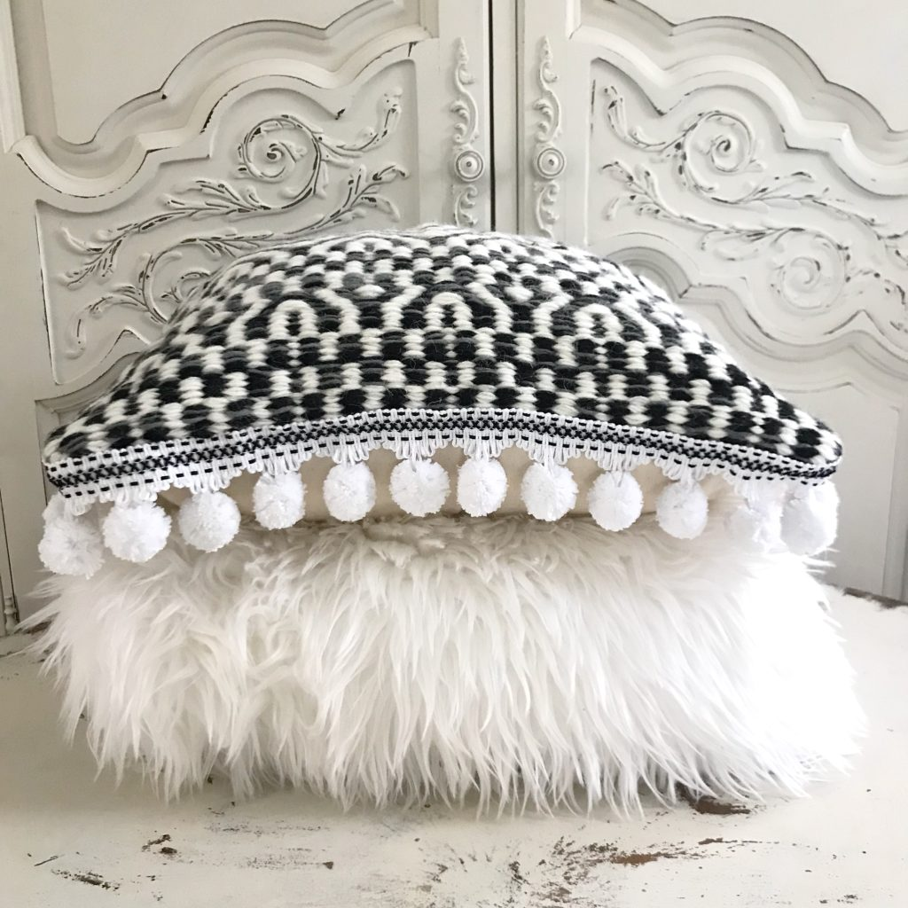 fur white pillow laid flat with black and white pillow with pom poms on edge laid on top