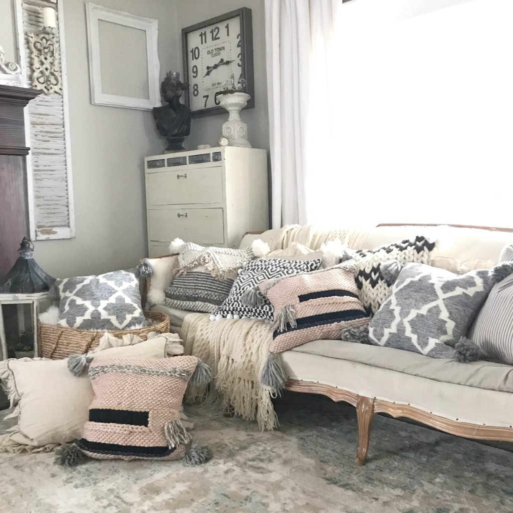white couch with 7 pillows on it and 2 farmhouse pillows on the ground and then one in a basket next to the couch