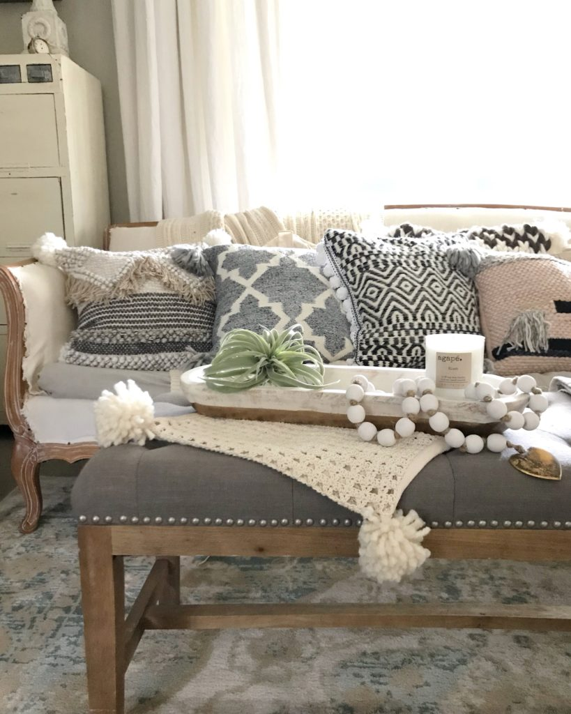 white couch with 5 chunky knit pillows and gray cushion foot rest. with gold and white dough bowl filled with wood bead garland and candle