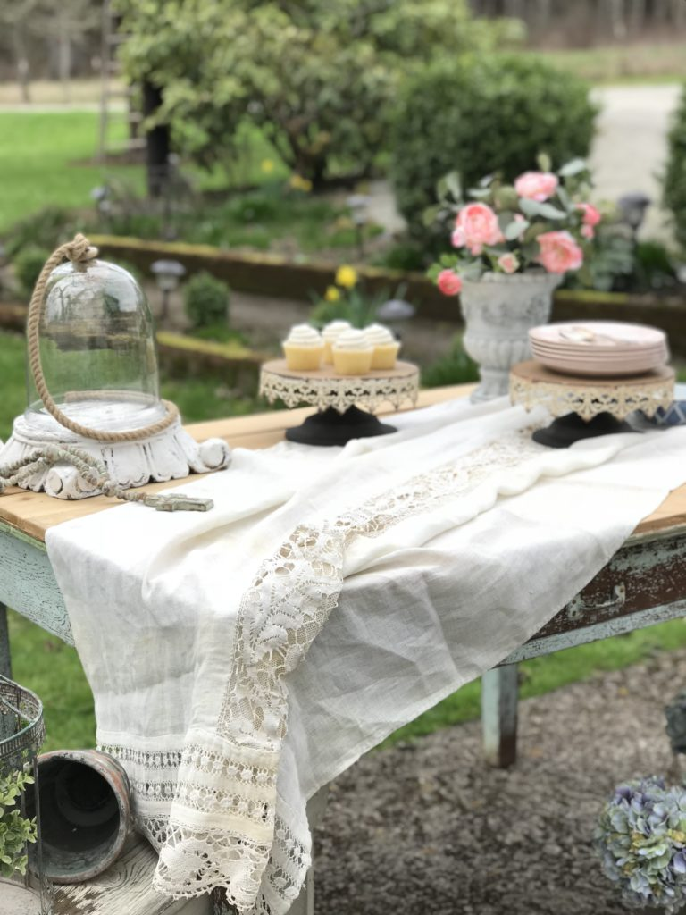 white linen sheet on farmhouse table. with 2 cake stands one with 4 white cupckaes and one with a stack of pink plates.