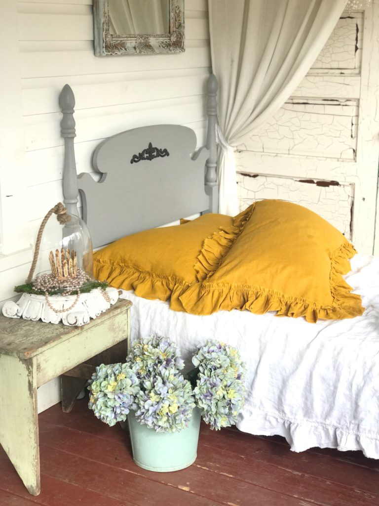 2 yellow linen pillows on white bed with gray twin bed frame. and hydrangeas on ground in blue bucket