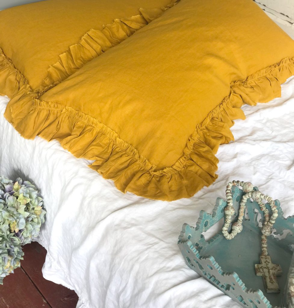 yellow linen shams on white bed spread with blue tray
