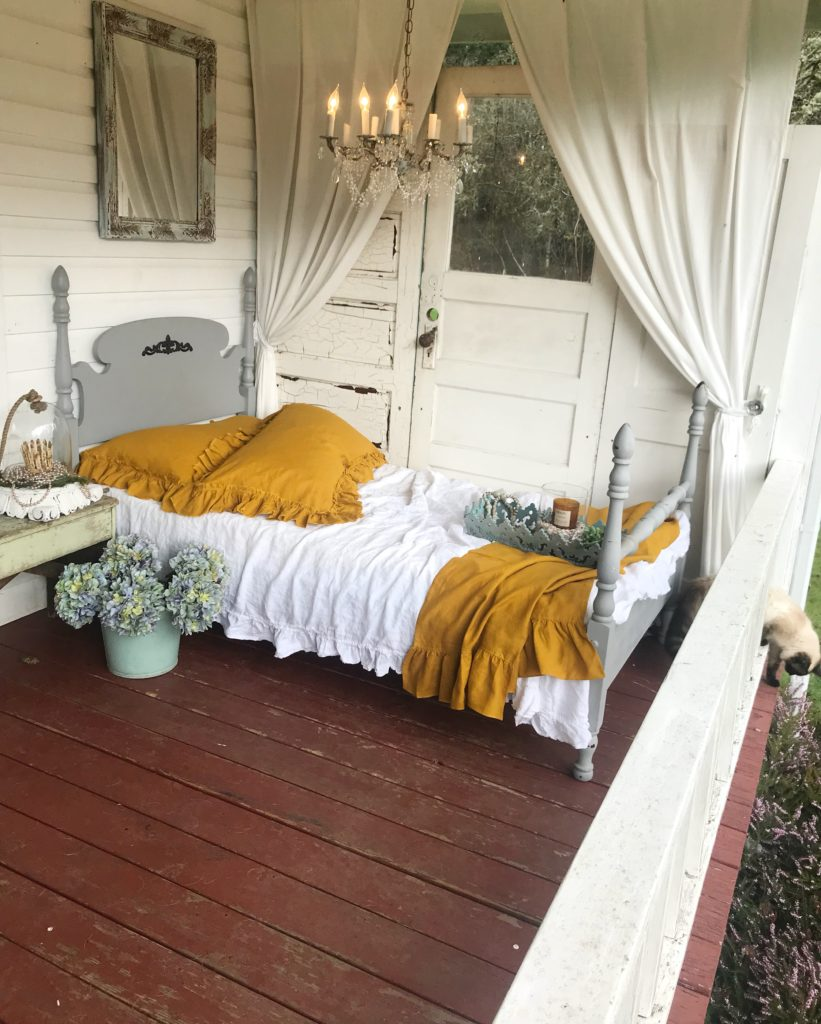 2 yellow pillow shams on white bed sleeping porch