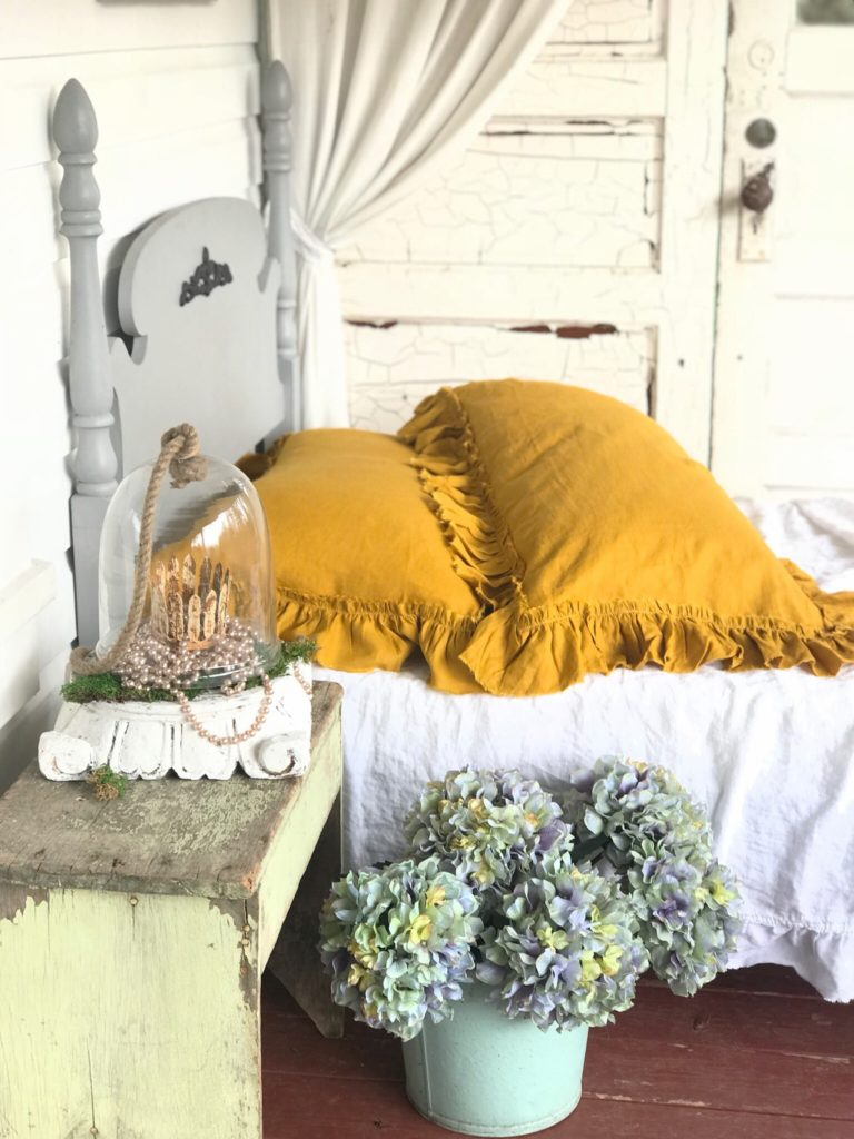 Yellow linen shams on white bed and gray twin bed frame. hydrangea in blue bucket on ground and green antique bench with white pedestal on top
