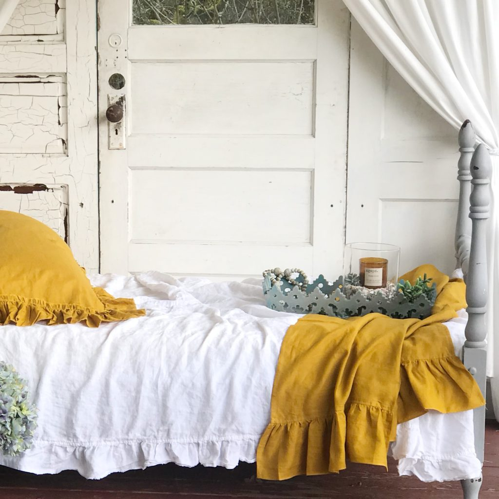 white ruffle bed with yellow pillows and linen bed blanket with blue tray sitting on bed