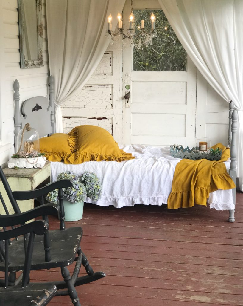 Incorporating Mustard Yellow in Shabby Chic Style napping porch with yellow pillows and bed blanket with white bedding. gray twin bed frame and chandelier over bed