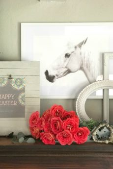 red bouquet of roses in a blue tray with cross bead garland in front of a happy easter printable with whit horse icture hanging