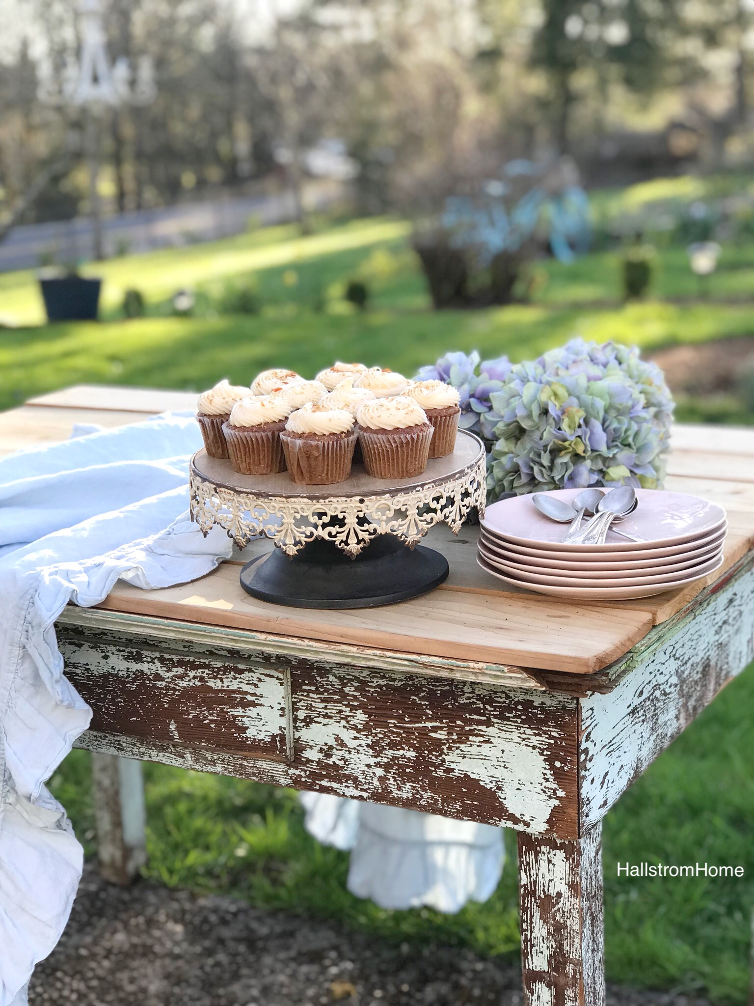 white rustic cake stand with 10 white frosted cupcakes and stack of pink plates with silver spoons ontop. bouquet of blue hydrangeas on a blue chippy farmhouse table