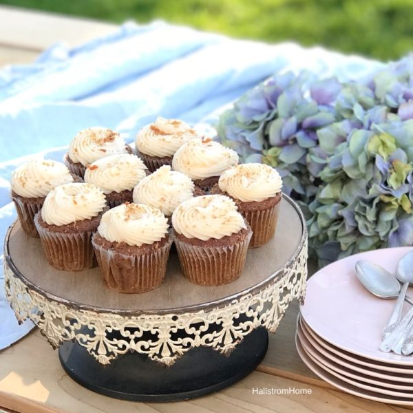 white rustic cake stand with 10 white frosted cupcakes and stack of pink plates with silver spoons ontop. bouquet of blue hydrangeas