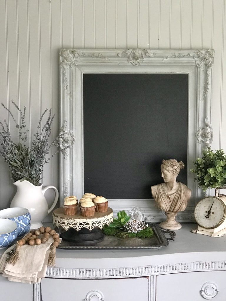 gray vintage chalkboard with white vase filled with lavender and cupcake tray with 4 white cupckaes and roman but