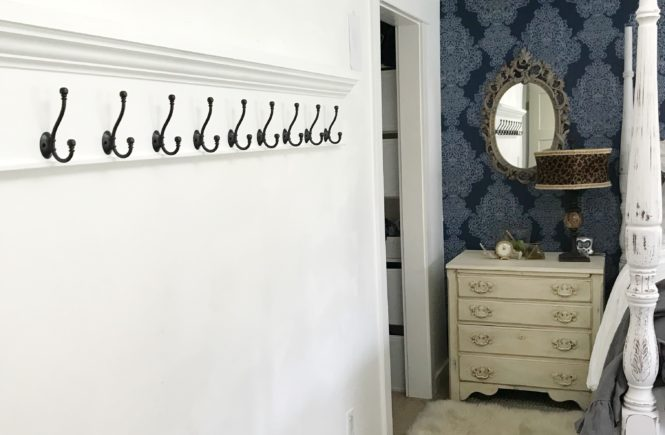 extra long coat rack hanging on white wall. other wall blue wallpaper with white dresser and oval mirror with leapord lampshade and fur rug