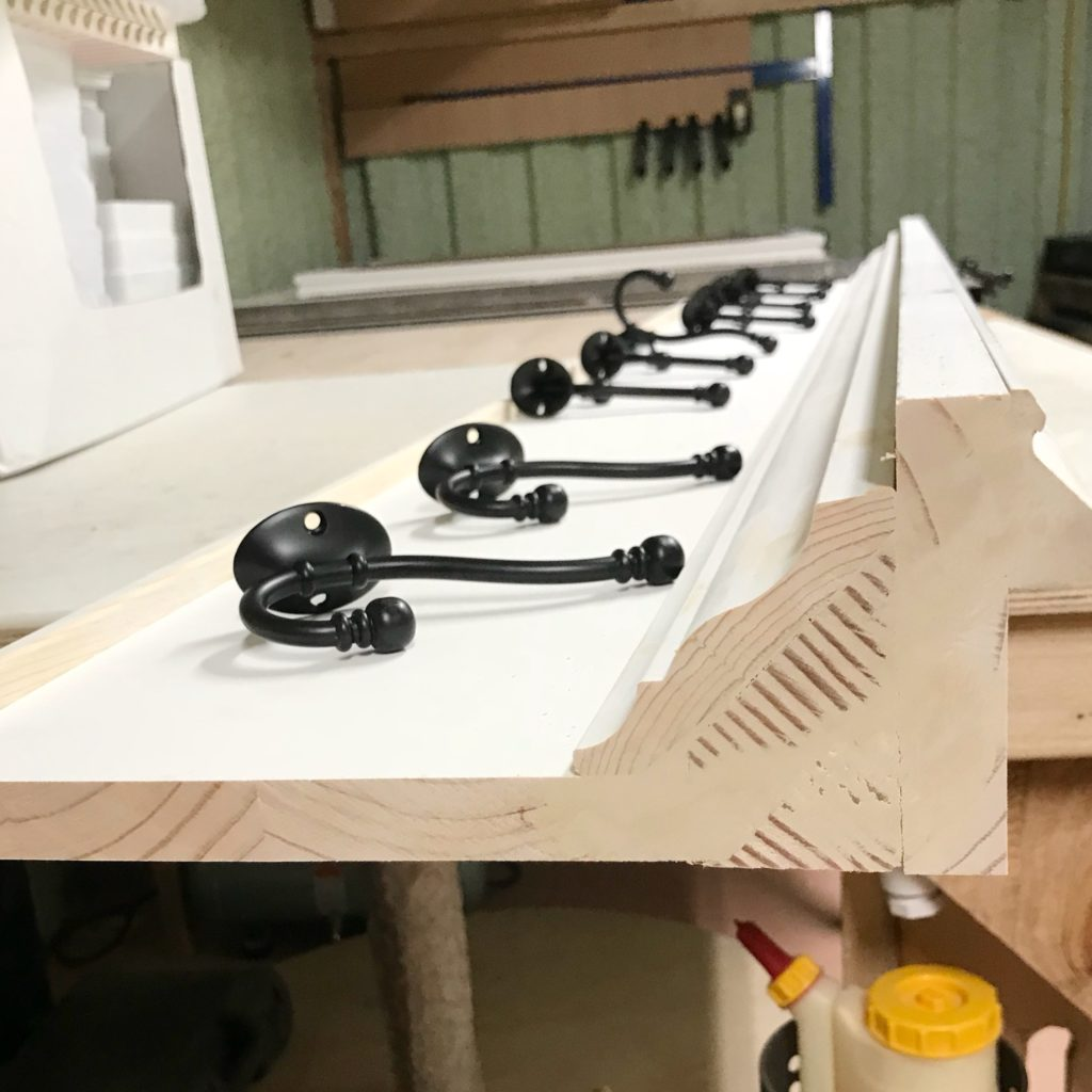 side view of wall coat rack with hooks laid out