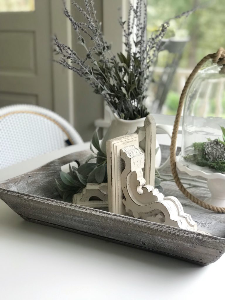 white table with wood tray filled with white corbel and white vase of lavender and cloche with rope
