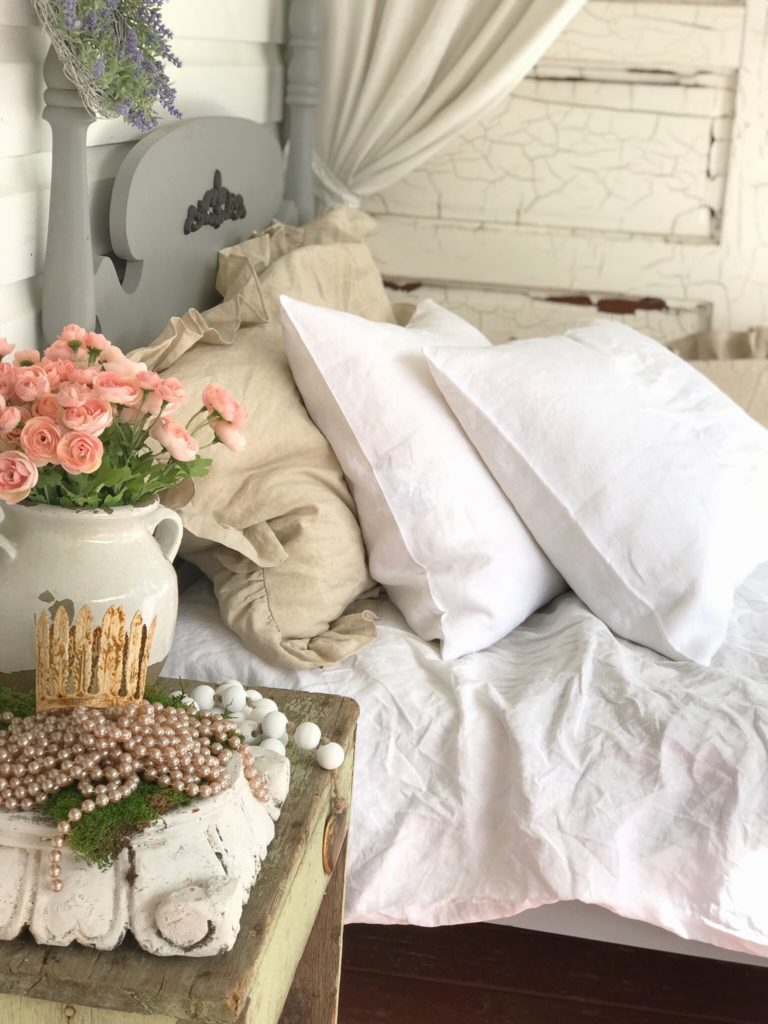 2 white linen pillows and ruffle brown pillows on white bed