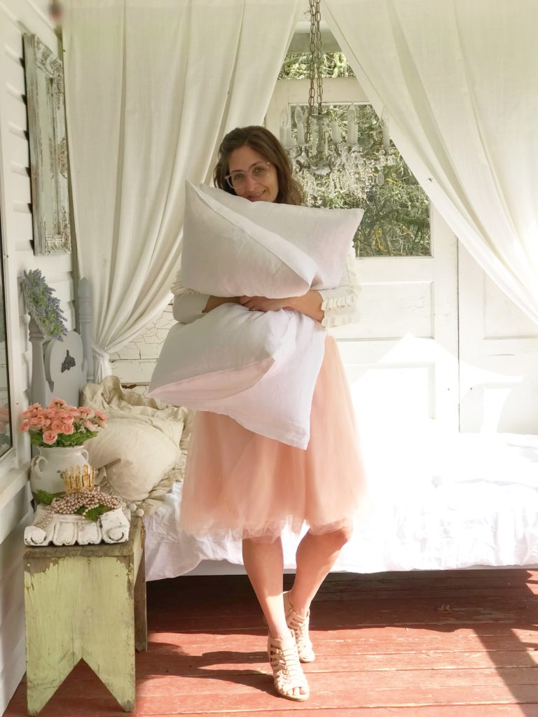 rhonda hallstrom in pink skirt holding 2 white linen pillows