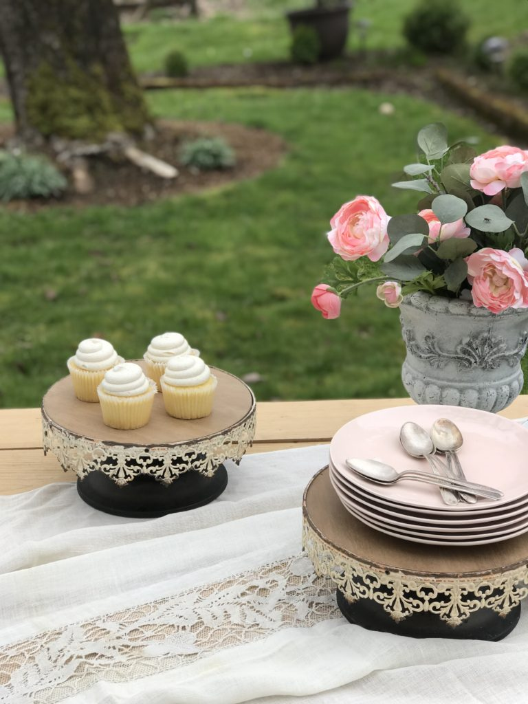 2 cake stands one with 4 white cupckaes and one with stack of pink plates