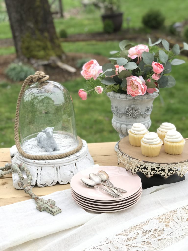 Vanilla Lavender Cupcakes Filled with Lemon Buttercream Frosting stack of pink plates with silver spoons on top. cake tray with 4 white cupcakes. a urn filledwith pink flowers and a glass jar on a pedestal