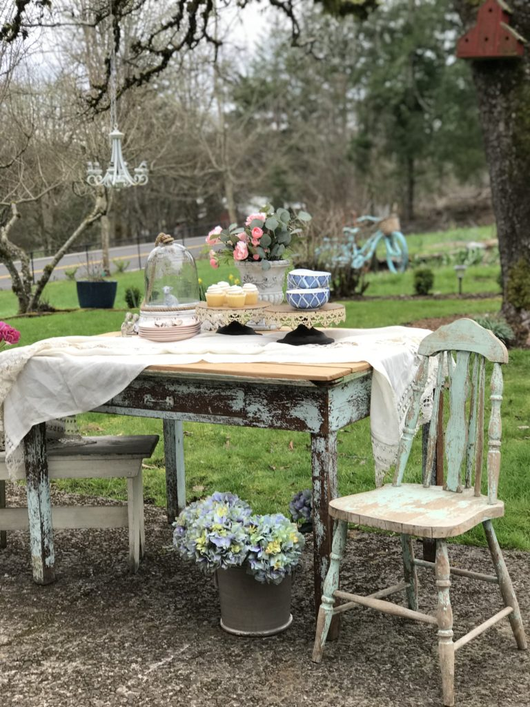 blue farmhouse table and chair with white table cloth and 2 cake stands