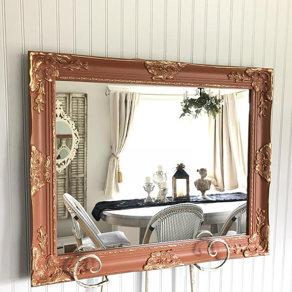 orange and gold overlay mirror on easel with table and chairs in reflection