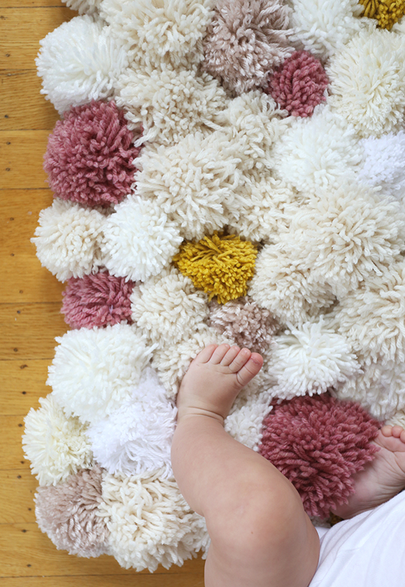 white and pink and yellow pom pom rug with baby legs on it