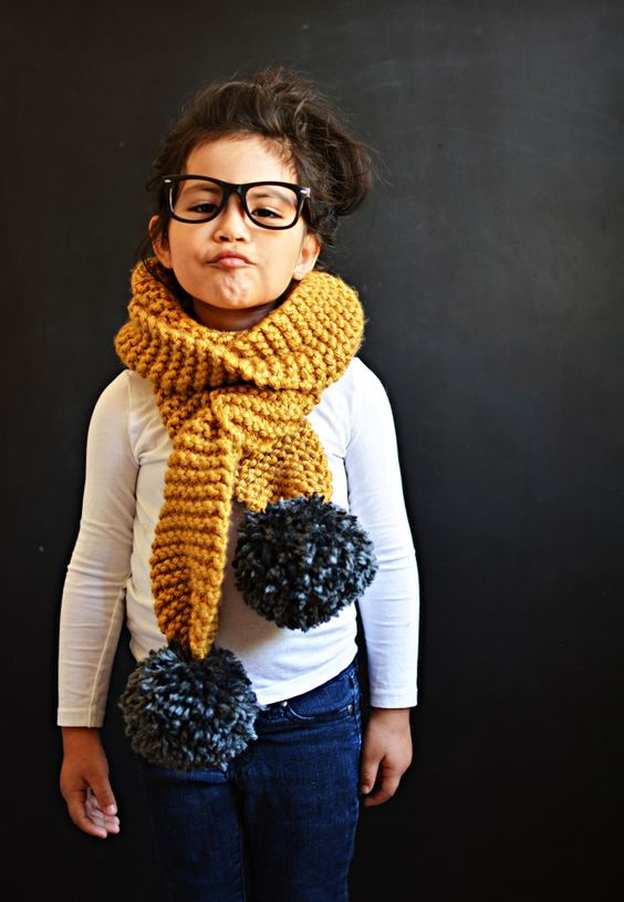 little brown haired girl with glasses and chunky yellow scarf with black pom pom on each end
