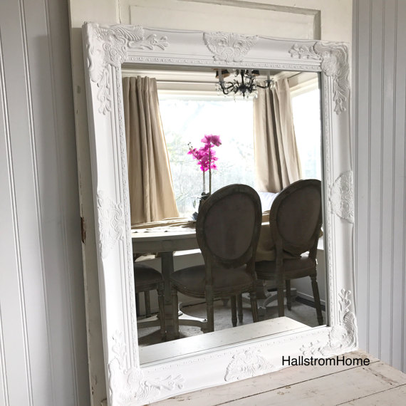 white mirror sitting on cream table in reflection is chairs and table with pink flower
