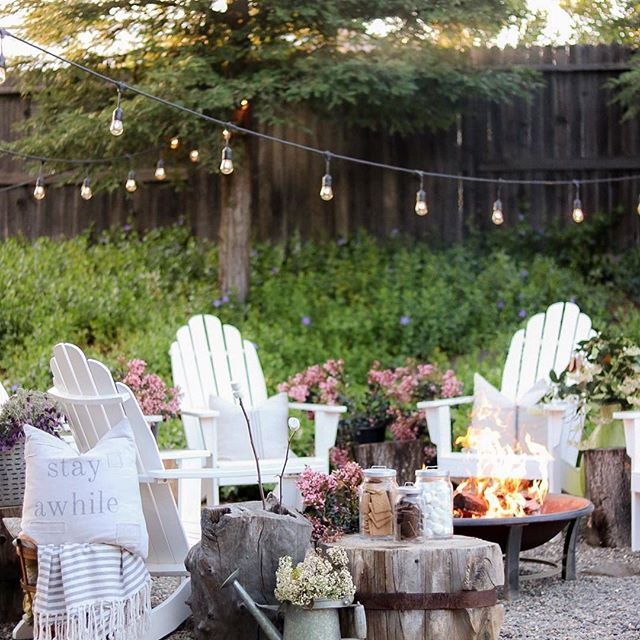 white lawn chairs around metal fire pit. wood side table with pink flowers and small jars filled with smores