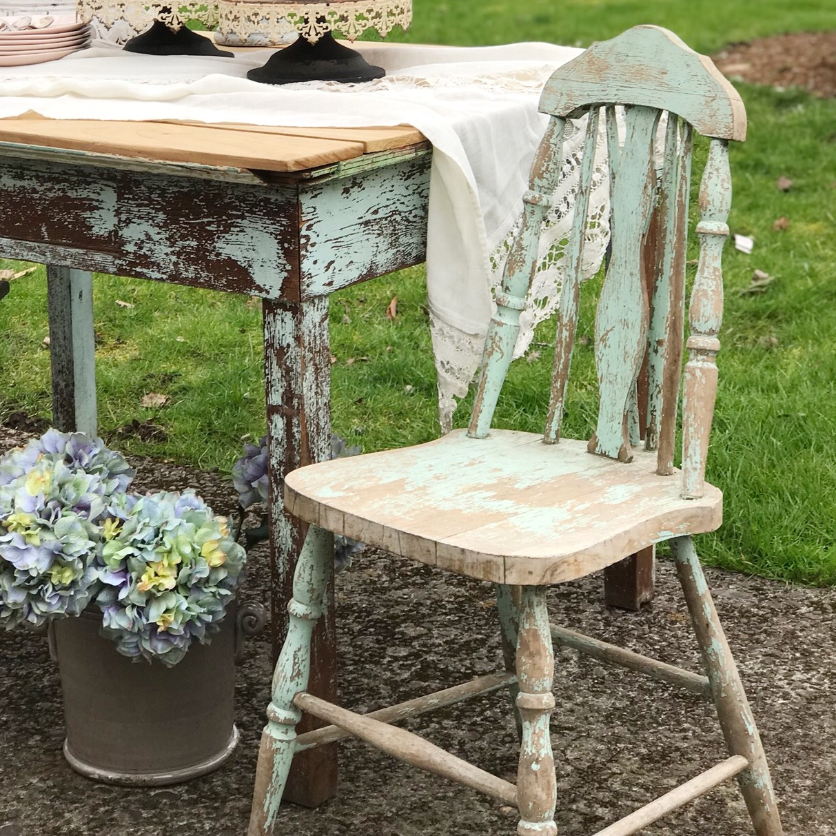 Our Farmhouse Decor from HallstromHome blue chippy chair next to antique blue chippy wood table with pot on ground with hyrdrangea bouquet