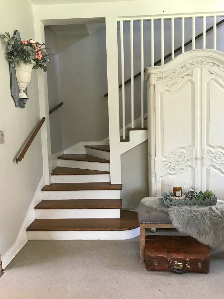 stair way with large white armoire and tufted gray bench in front