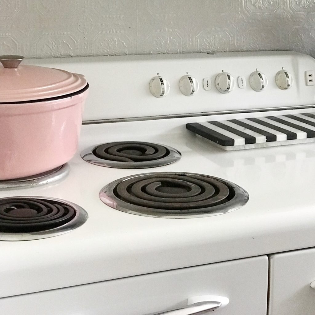 stove top white with pink pot ontop with black and white stripe cutting board