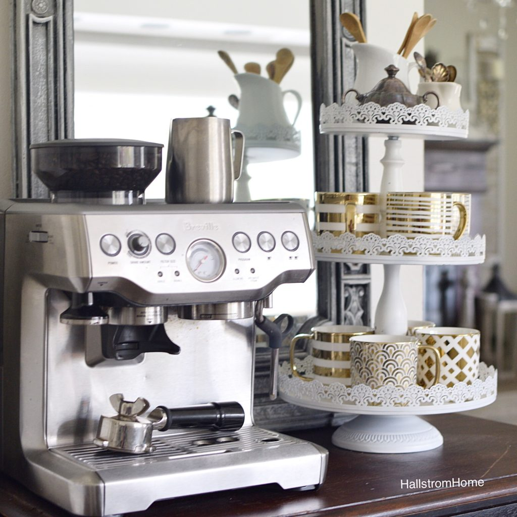 breville coffee machine with 3 tier tray filled with white and gold mugs