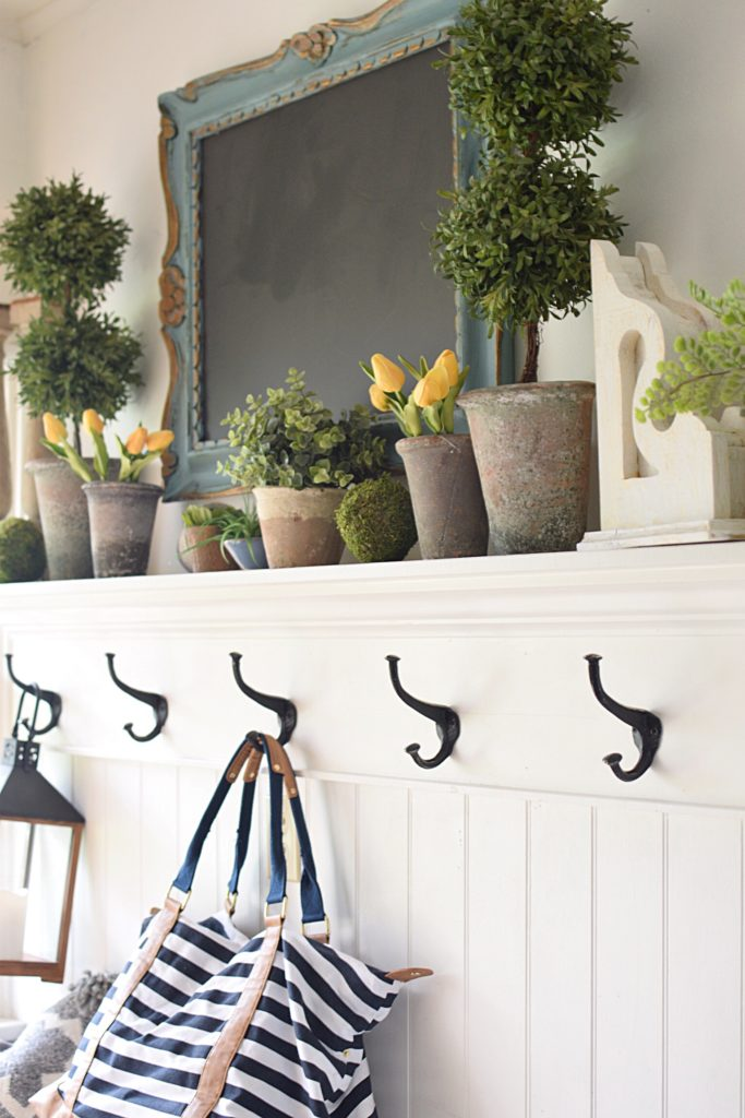 mudroom hooks with pots on mantel with yellow tulips and blue chalkboard
