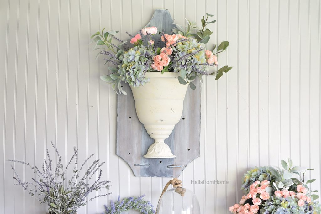 wall pot filled with pink and green and purple flora with lavender bouquet below and cloche