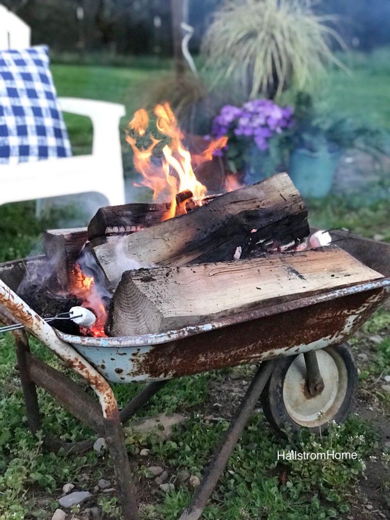 rusty blue wheel barrow fire place white white chair in background and purple flowers