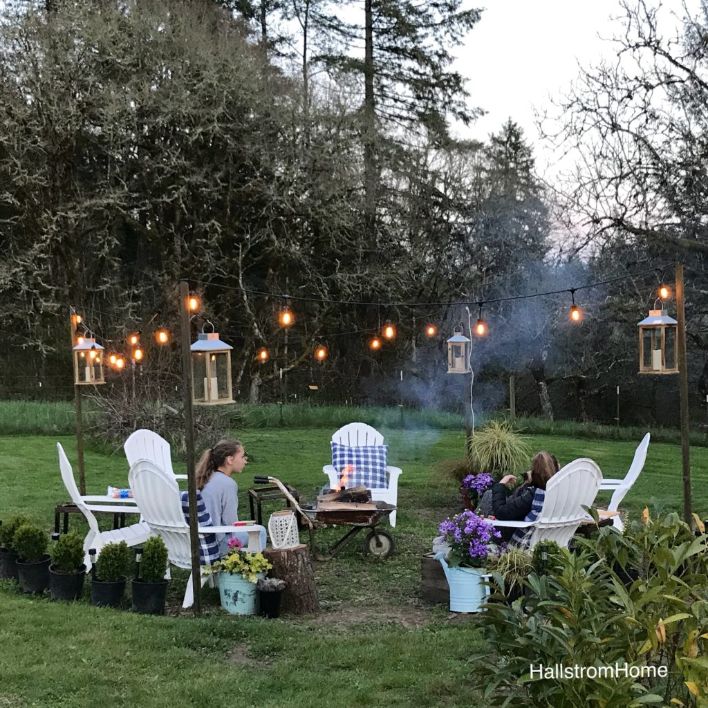 The Girl Who Built a Beautiful Fire Pit white lawn chairs around heelbarrow lit fire. lights draped around border seating area