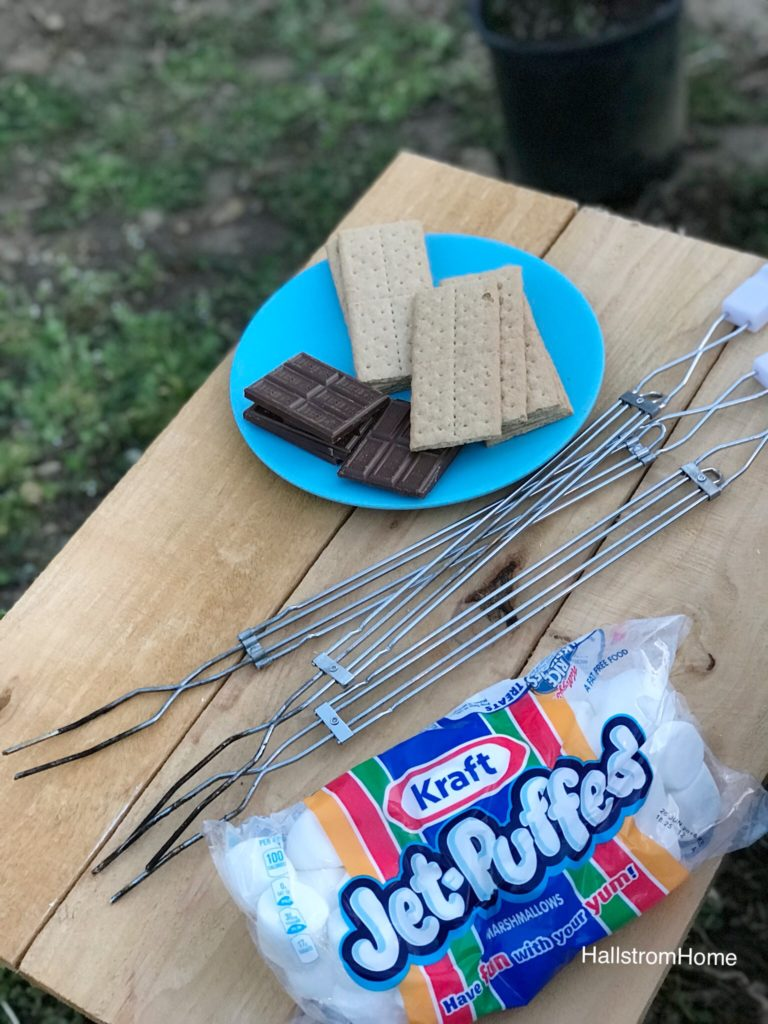 blue place with stack of chocolate and graham crackers with roasting sticks and marshmallow bag on wood table