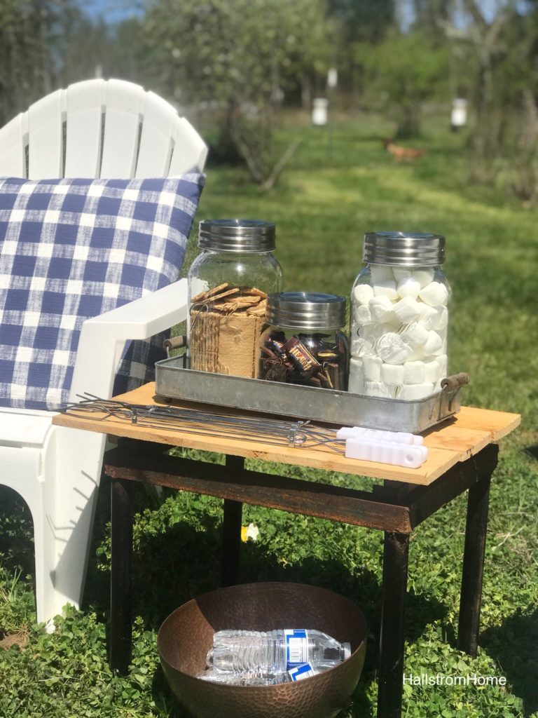 wood side table top with 3 jars filled with marshmallws, chocolate, and grahamcrackers