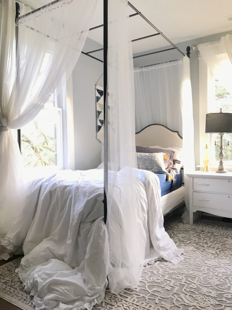 Part 2: Our 100 Year Old Farmhouse Spring Tour canopy twin bed with white canopy. white ruggle sheet draped off bed with blue sheets and white nightstand