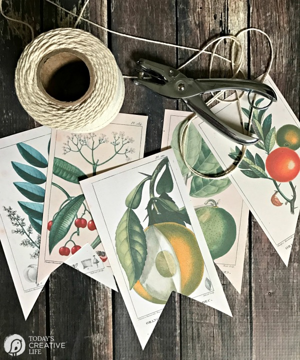 5 banner pieces with botanical prints on them and a spool of twime and hole puncher laying on wood table