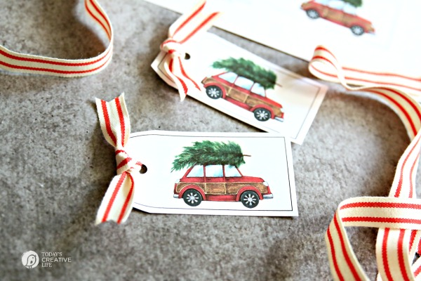 vintage red car with christmas tree on top gift tag printables with red and white stripe ribbon tied to them