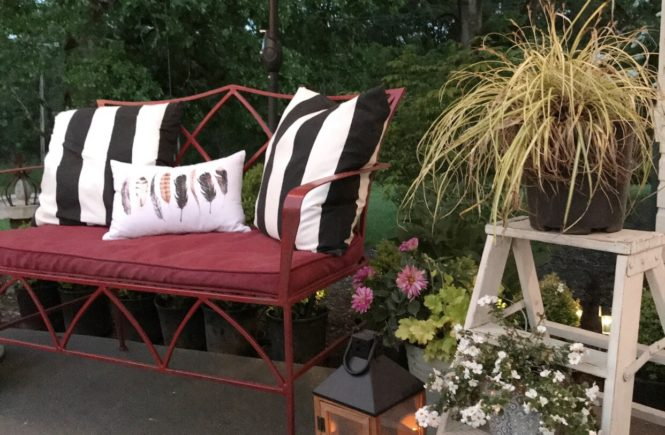 red bench with black and white stripe pillows and outdoor lantern on ground