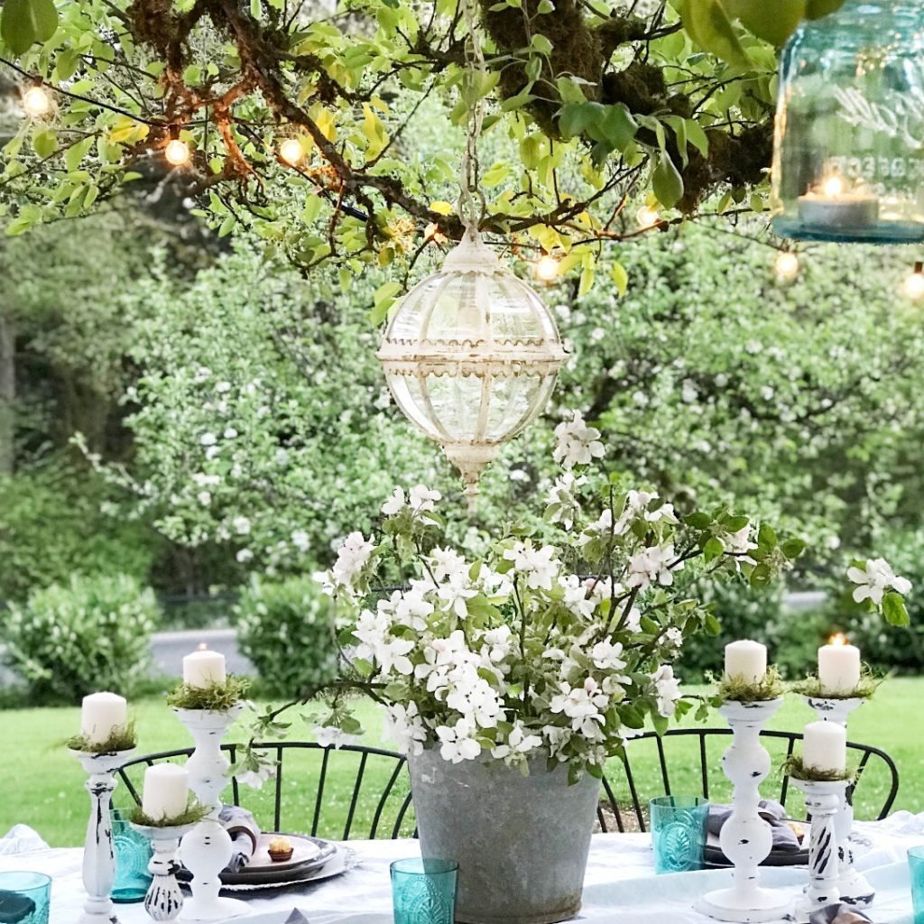 Outdoor Farmhouse Dining Made Easy white linen table cloth with 6 white candle holders with white candles and greenery. silver bucket holding white and green flowers round glass chandeiler hanging above in trees