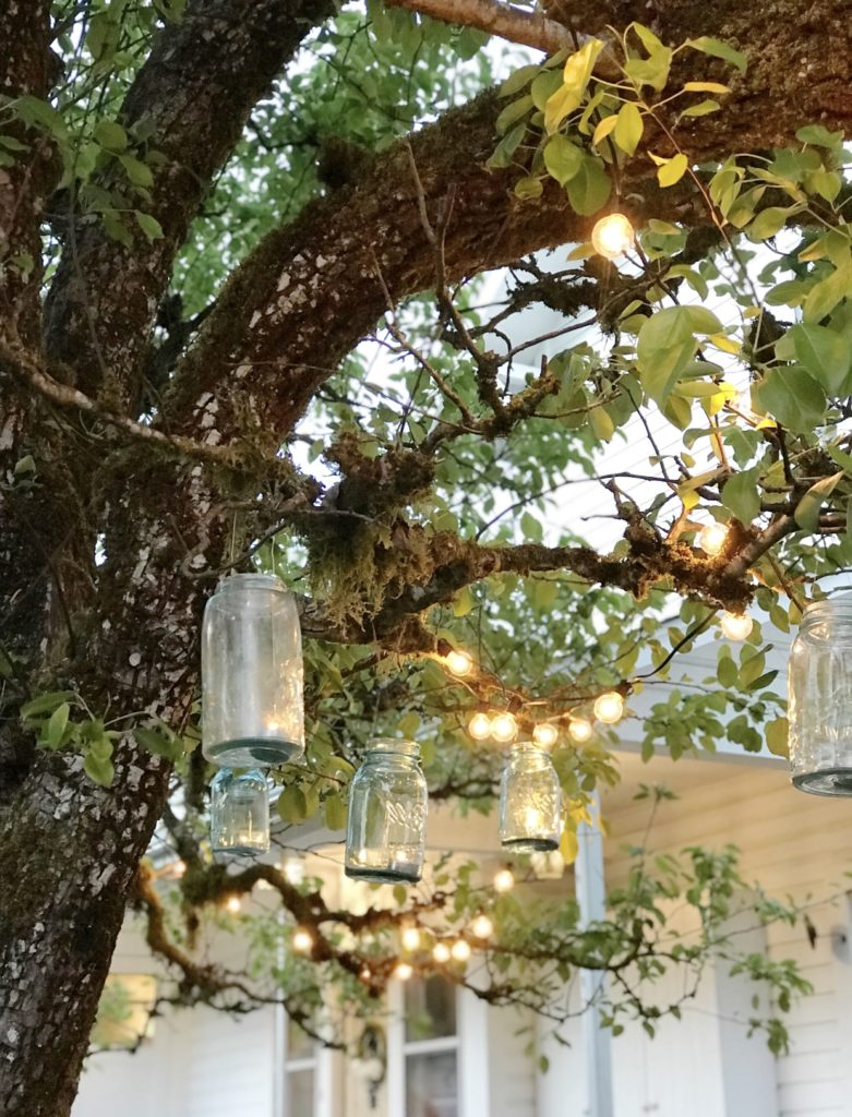 3 blue mason jars hanging from tree with lights