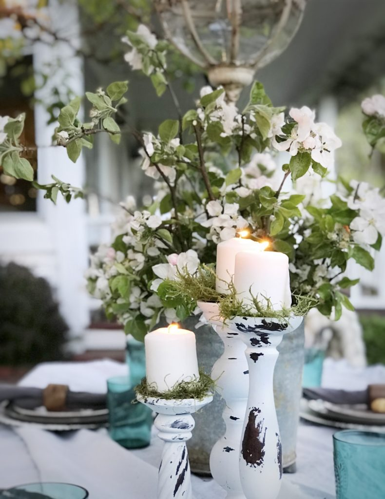 3 white distressed candle holder on outdoor table. silver bucket with white flowers and greenery