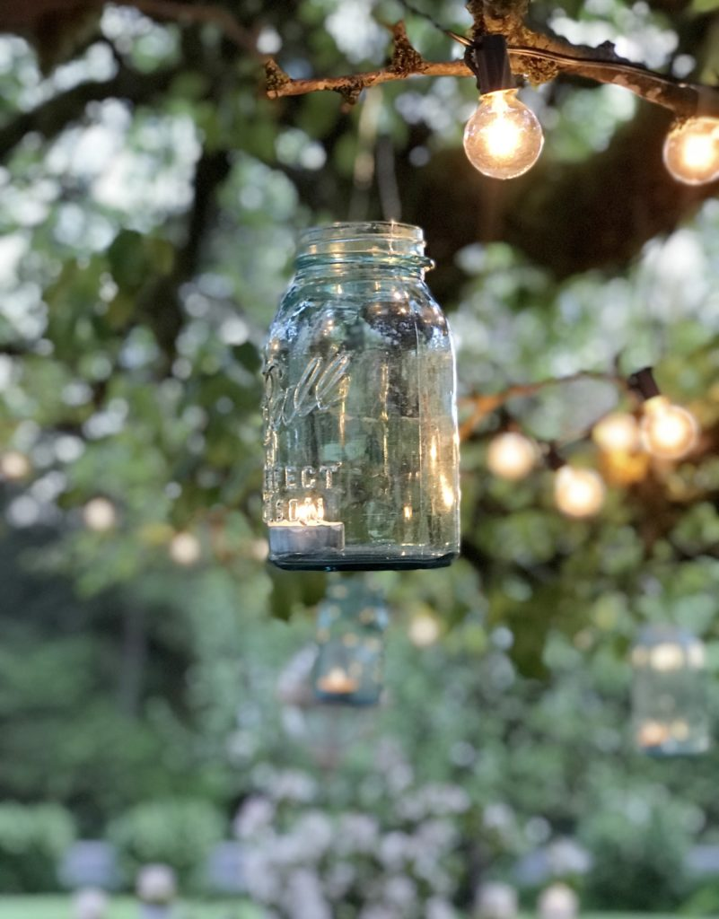 1 blue mason jars hanging from tree with lights