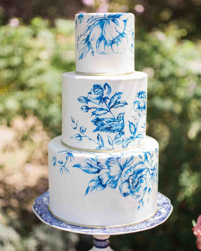 white cake with blue paint work of flowers