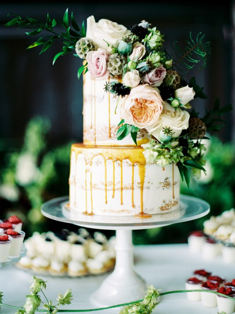 2 tier naked cake with dripping caramel and rases and greenery
